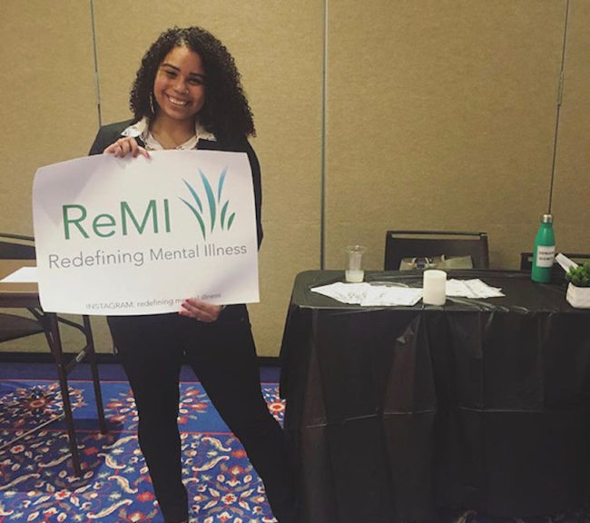 India with a poster from her organization Redefining Mental Illness (ReMI).