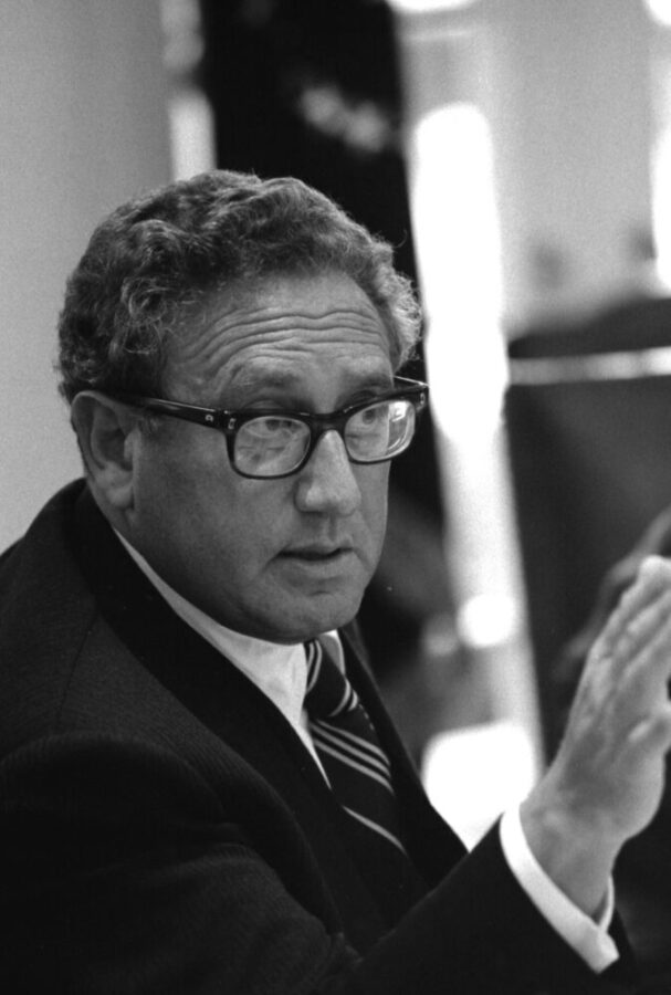 Black and white photo of Henry Kissinger with his hand pointed at someone.