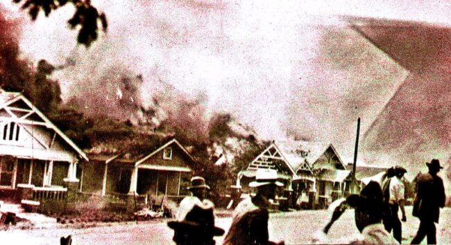 A mob of white rioters burn houses in Tulsa in 1921