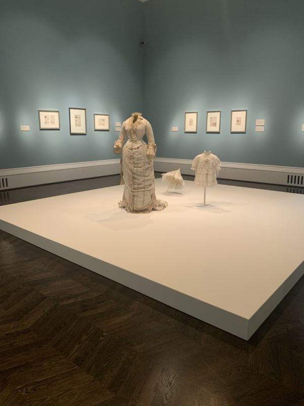 """The dress and parasol are a part of the """"Stepping Out"""" portion of the exhibit and display what people wore in public in 19th century Europe."""