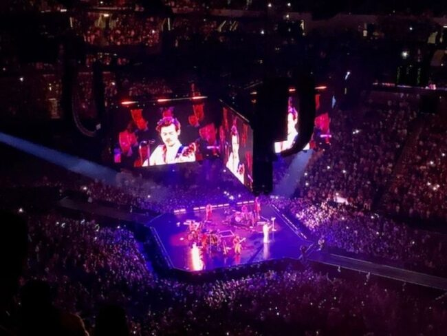 A jumbotron of Harry Styles above the audience in the American Airlines Stadium.