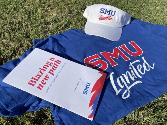A blue shirt, white cap, and white brochure arranged on a green lawn